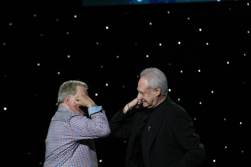 Brent Spiner and William Shatner share an elbow bump in greeting
